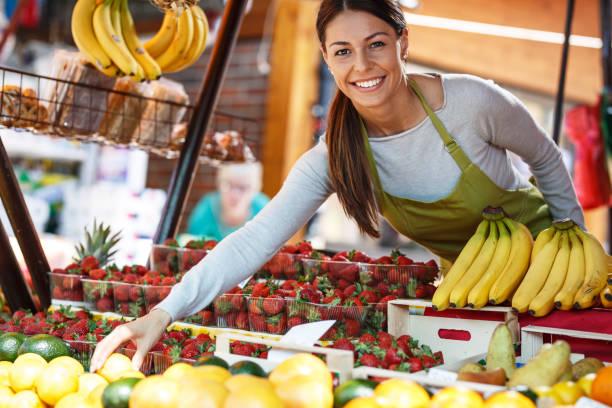 young attractive fruit market saleswoman - bazar mercato foto e immagini stock