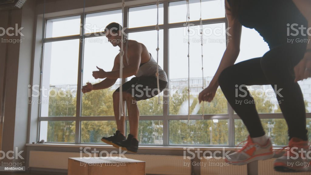 Young attractive girl and muscular man fitness instructor doing box jump exercise during a workout at the gym stock photo
