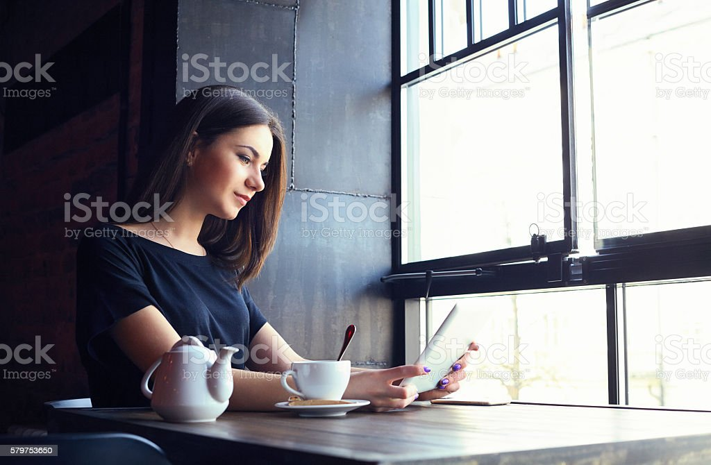 Young attractive girl in coffee shop working on tablet computer stock photo