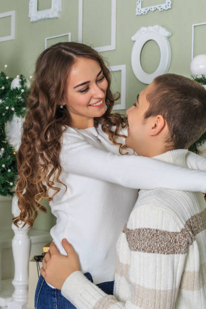 Young attractive girl is hugging her boyfriend and smiling stock photo