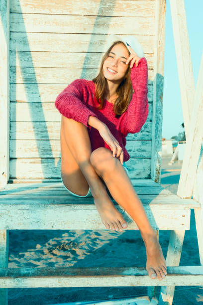 Young attractive girl posing smiles at a lifeguard tower. Red sweater and hat. stock photo