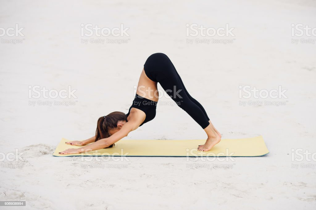 Young attractive girl practicing yoga, doing Downward facing dog exercise. stock photo
