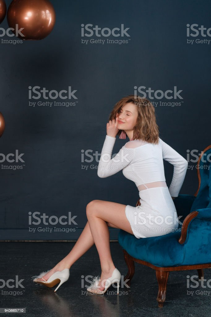 Young attractive girl sitting on a chair on black background, wearing white evening skirt and shirt stock photo