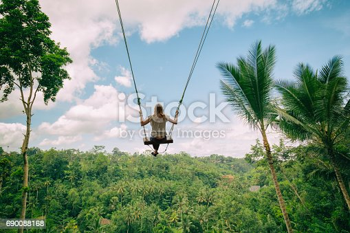 istock Young attractive girl swinging in nature. 690088168