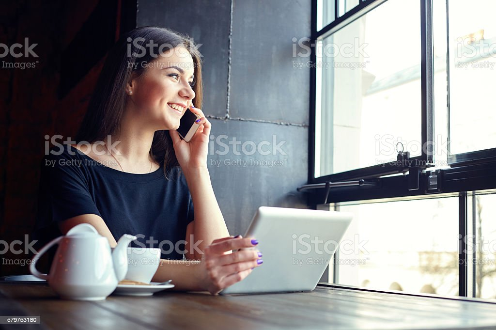 Young attractive girl talking on mobile phone in coffee shop stock photo