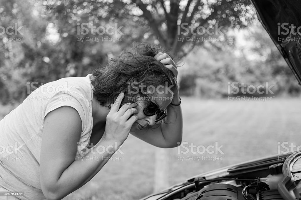 Young attractive girl with a broken car stock photo