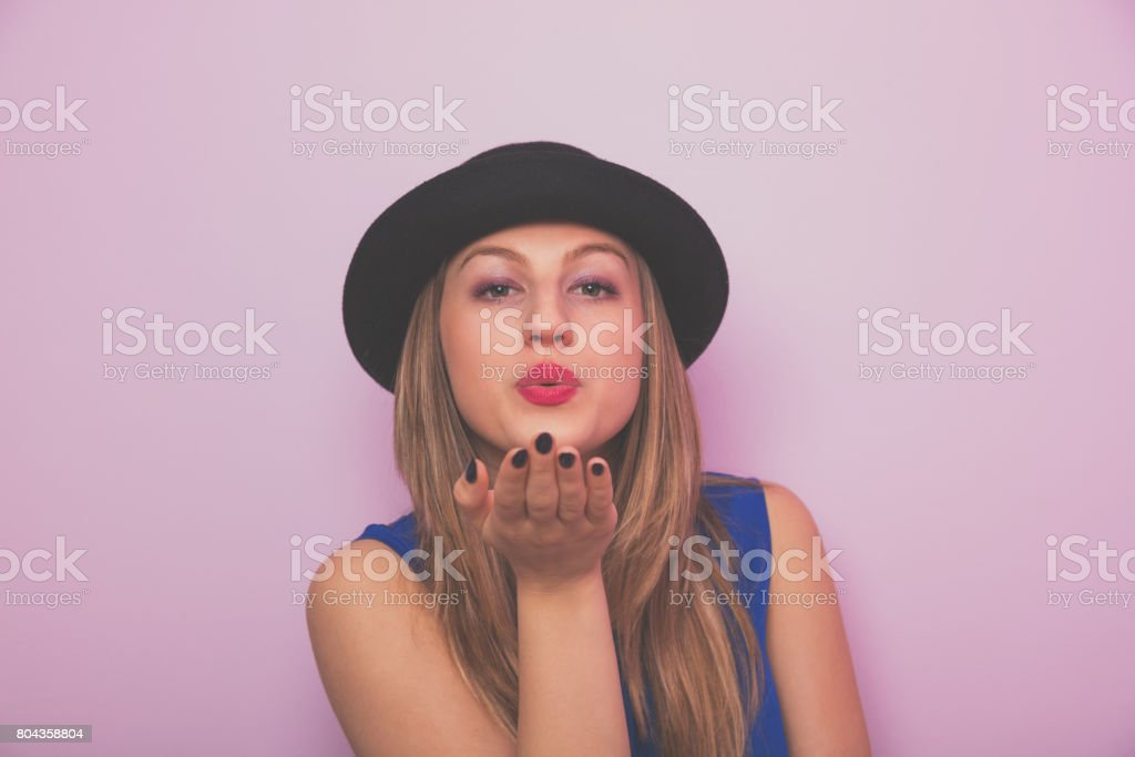 Young attractive girl with hat sending air kiss. stock photo