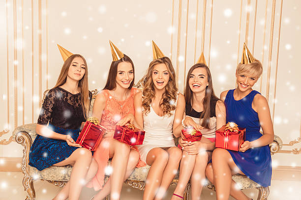 Young attractive girls with presents having xmas party – zdjęcie