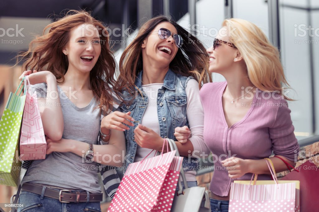 Young attractive girls with shopping bags in the city stock photo