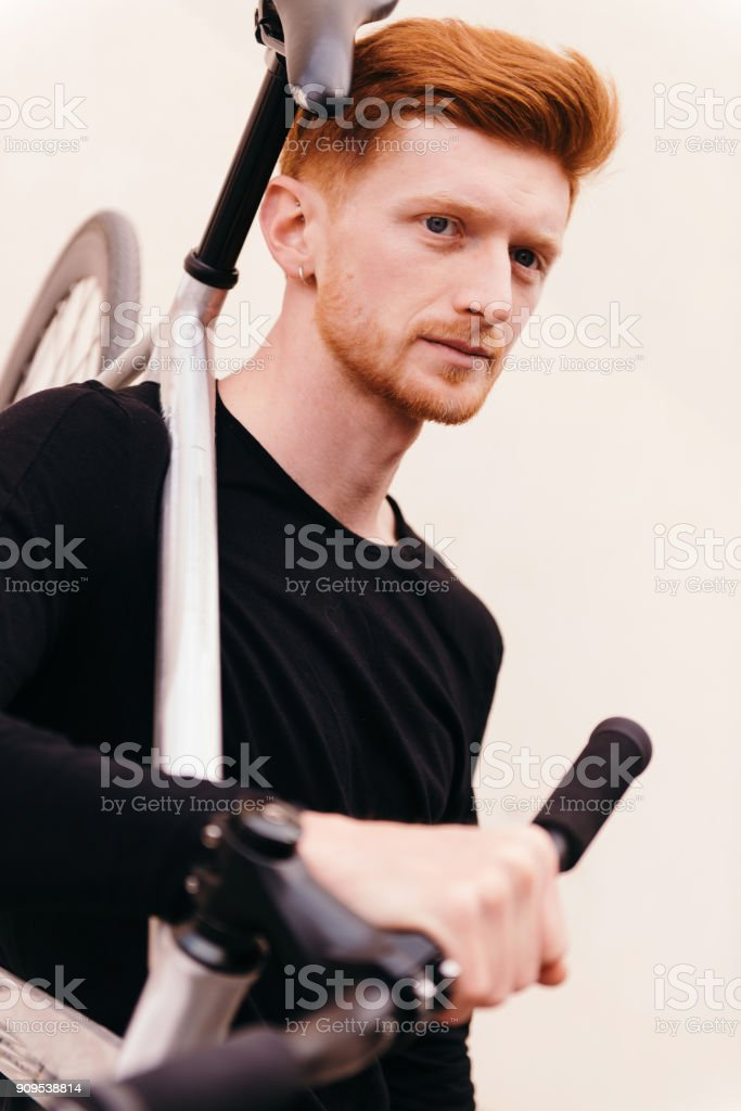 Young attractive guy with foxy hair and ginger beard and his fix bike stock photo