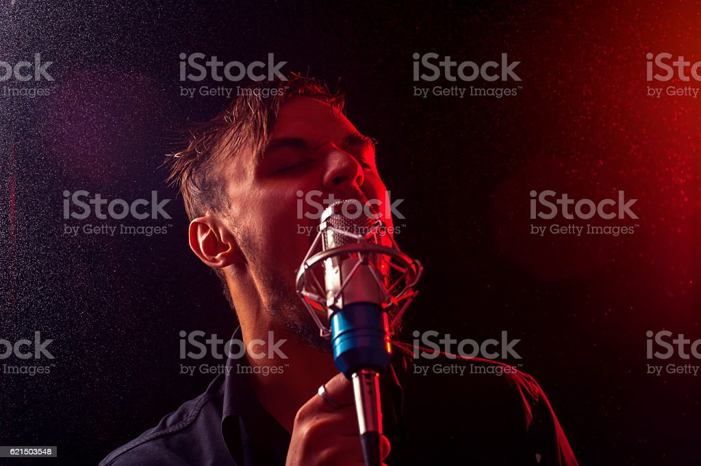 Young attractive guy with microphone on the stage foto stock royalty-free