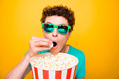 Young attractive handsome funky guy wearing casual green polo t-shirt and 3d sun glasses, eating pop corn, watching cinema. Isolated over vivid shine bright yellow background