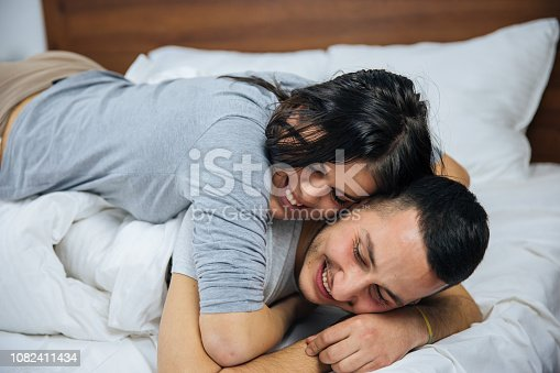Happy Young Playful Couple in Bed. Intimate Young Couple During Foreplay in Bed.