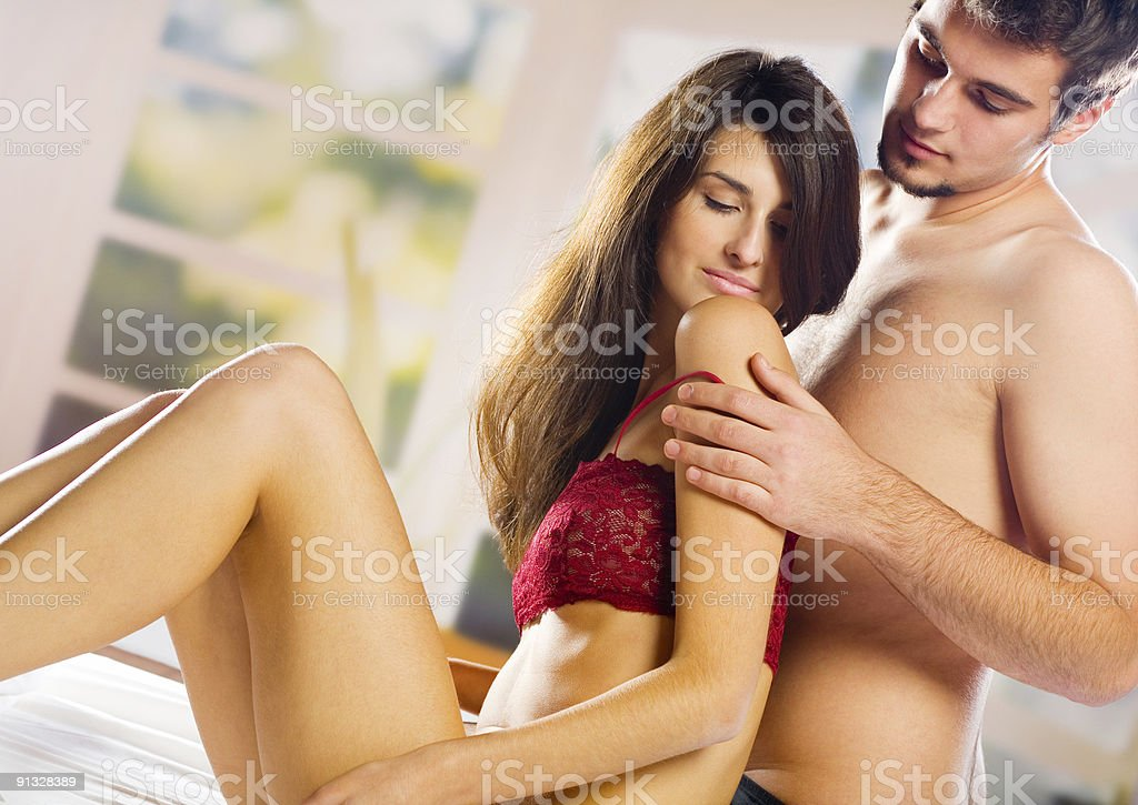 Young attractive happy couple embracing in bedroom stock photo