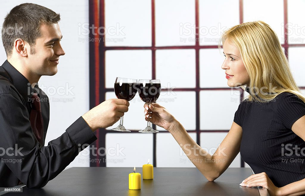 Young attractive happy smiling couple celebrating with red wine, indoors royalty-free stock photo