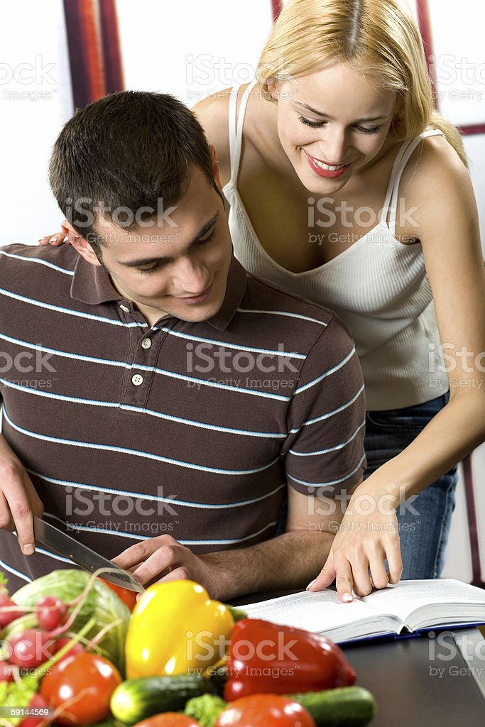 Young attractive happy smiling couple cooking at the kitchen royalty-free stock photo