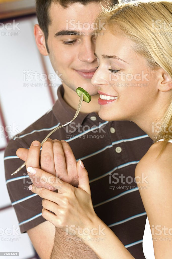 Young attractive happy smiling couple eating playfully vegetables, indoors royalty-free stock photo