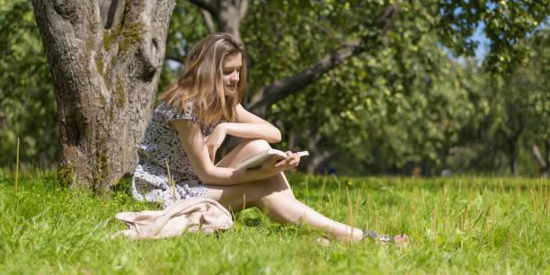 Mulher feliz atrativa nova que lê um livro em um pomar rural da maçã - foto de acervo