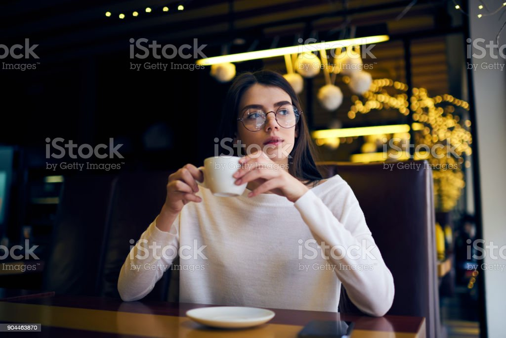 Young attractive hipster girl in eyewear enjoying aroma coffee thinking about plans for day while sitting in cafe, charming female starting day with americano for breakfast concentrated on ideas stock photo