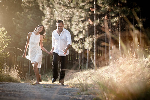 Young attractive indian couple laughing through grass field Young attractive indian couple laughing through grass field romance stock pictures, royalty-free photos & images