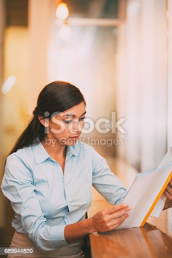 istock Young Attractive Indian Woman Reading Book in Cafe 689944820