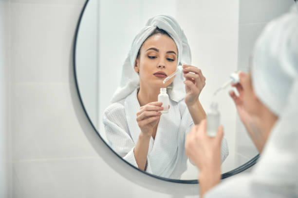 Young attractive lady taking care of her facial beauty at home stock photo