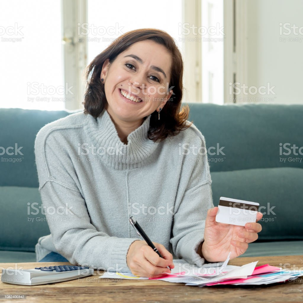 Young attractive latin business woman looking happy and satisfied with credit debit card advantages and use and accounting costs, charges, taxes and mortgage with calculator on sofa at home . stock photo