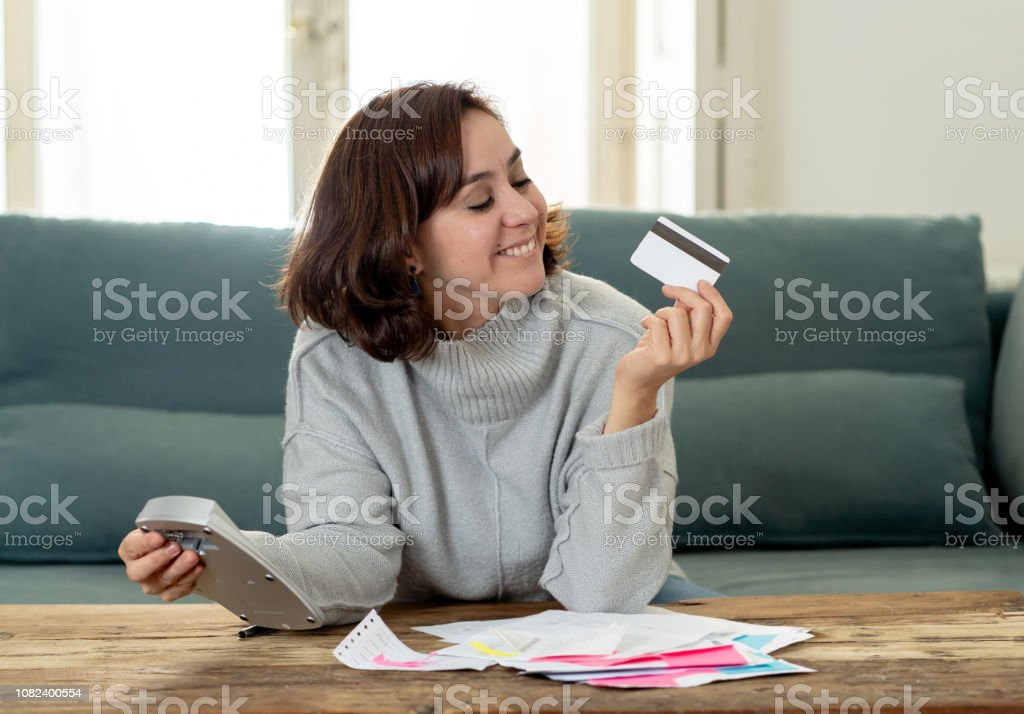 Young attractive latin business woman looking happy and satisfied with credit debit card advantages and use and accounting costs, charges, taxes and mortgage with calculator on sofa at home. . stock photo