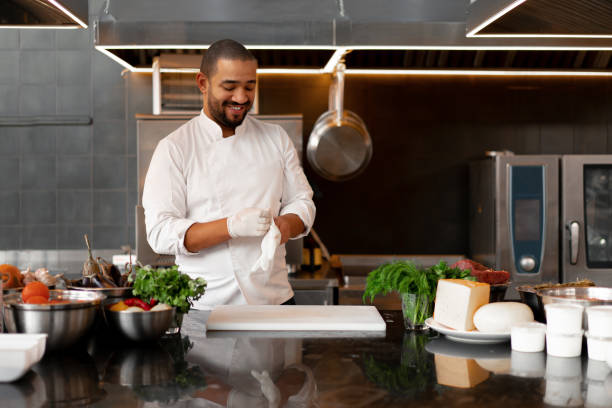 young attractive male cook blows up his protective glove jokes and has fun in the professional kitchen young attractive male cook blows up his protective glove jokes and has fun in the professional kitchen Handsome black chef dressed in white uniform on workplace chef stock pictures, royalty-free photos & images