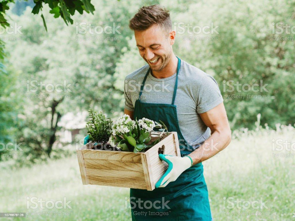 Junger attraktiver Mann trägt eine Holzkiste mit Pflanzen und Blumen. Er schaut sie an und lächelt. Er ist im Bereich als Gärtner verkleidet – Foto