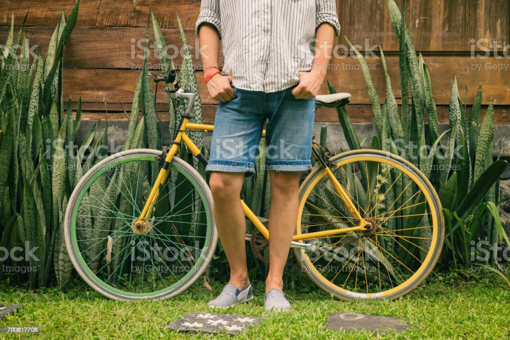 Young attractive man enjoying outdoors with old bicycle. stock photo