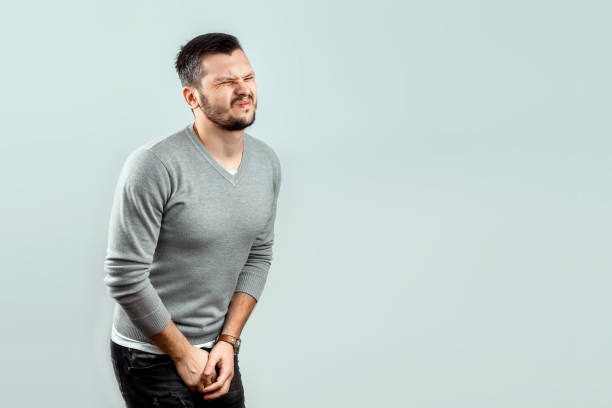 A young, attractive man feels pain in his groin, arms folded between his legs. Experiencing pain, male problems, potency. A young, attractive man feels pain in his groin, arms folded between his legs. Experiencing pain, male problems, potency. reproductive organ stock pictures, royalty-free photos & images
