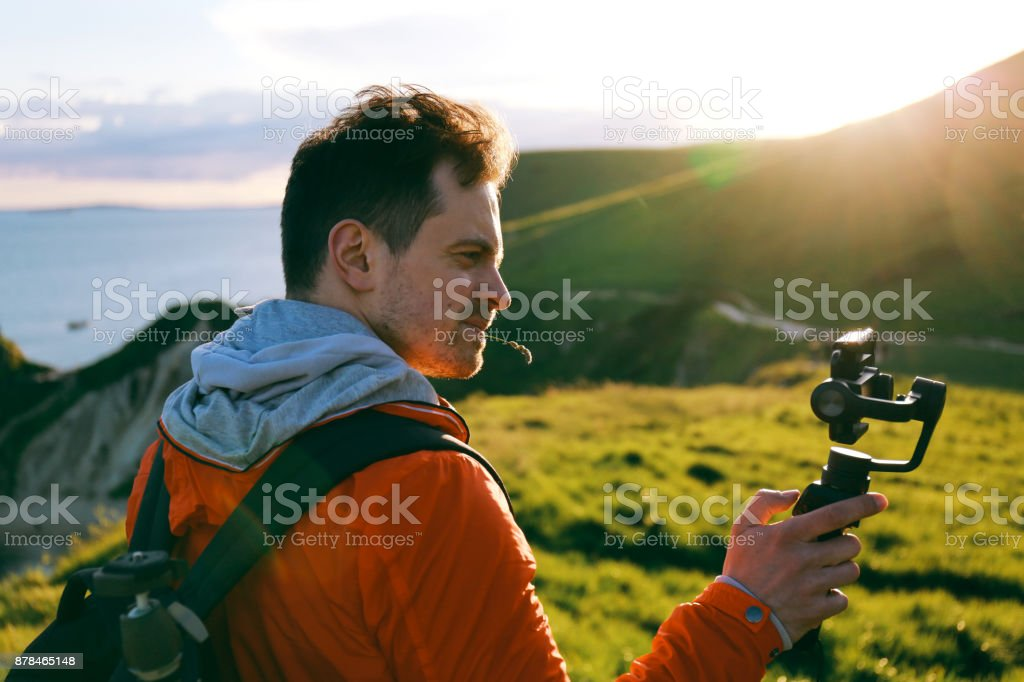 Young attractive man films a travel video using a hand held stabiliser and smartphone stock photo