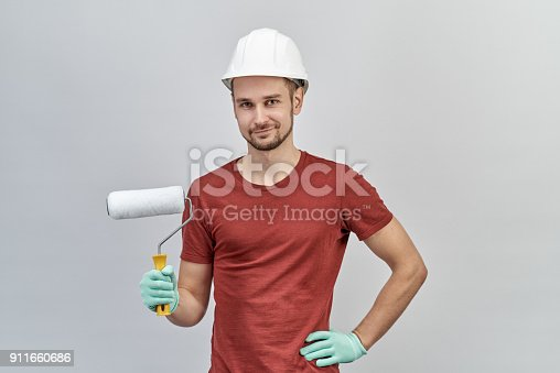 istock young attractive man in a red shirt, white protective helmet and gloves holding a roller to paint with happy and confident expression. 911660686