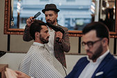 Young attractive man in barbershop, getting his hair styled by a barber