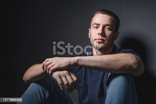 Young attractive man in blue jeans and a polo shirt sits on the floor near the wall in the studio. Youth and attractiveness concept.