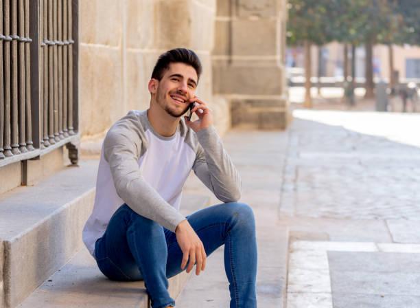 Junge attraktive Mann in seinen Zwanzigern glücklich sprechen und chatten mit Freund auf Social Media auf Smartphone auf Urlaub in Europa. In Kommunikation, Technologie Internet und Lifestyle-Konzept. – Foto