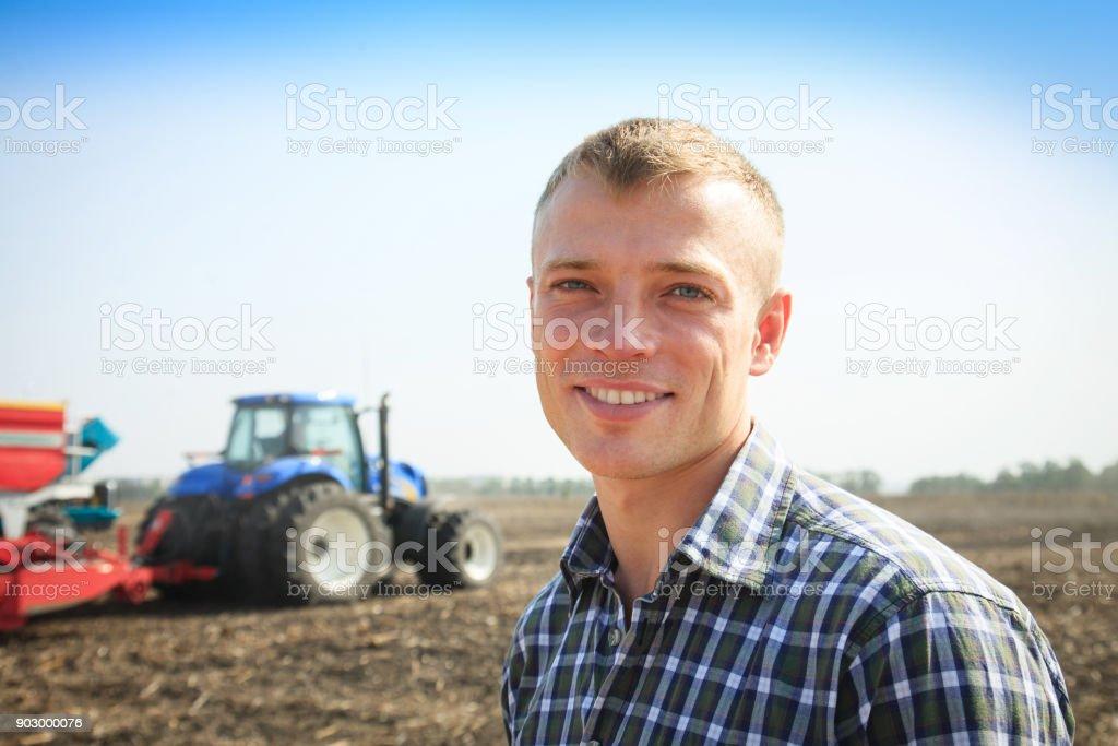 Jeune homme séduisant près d'un tracteur. Concept de l'agriculture. - Photo