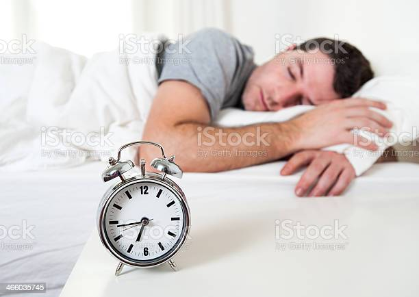 Joven Atractivo Hombre Durmiendo En La Cama Foto de stock y más banco de imágenes de Acogedor