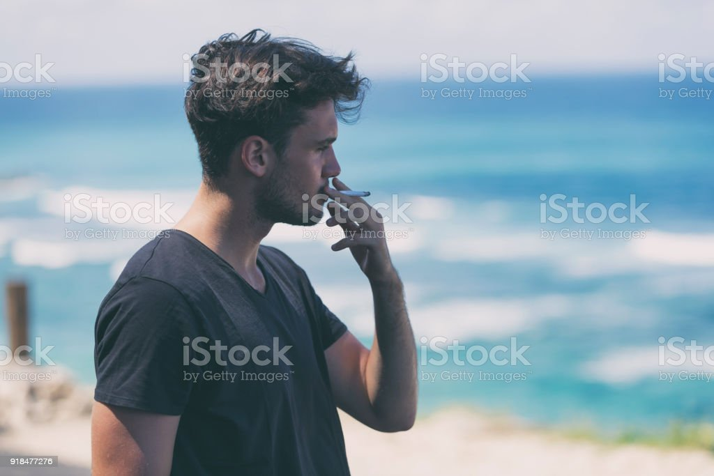 Young attractive man smoking cigar on the beach. stock photo