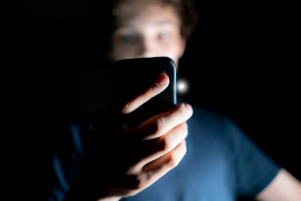 young attractive man use mobile phone late at night in a dark room b stock photo