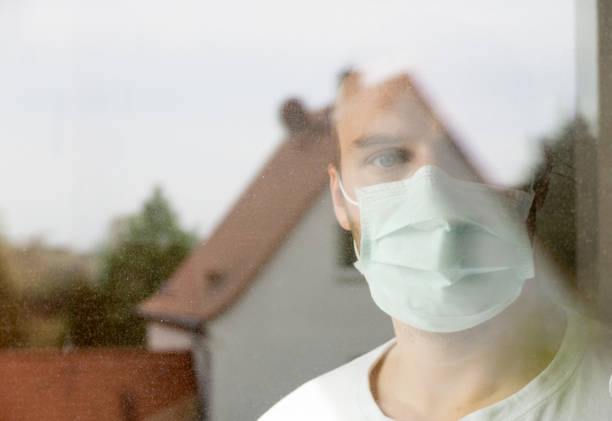 young attractive man with corona mask looks out of window stock photo