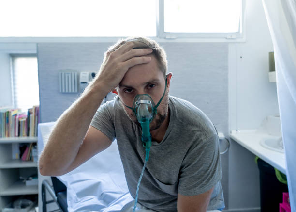 Junger attraktiver Mann mit Sauerstoffmaske sieht traurig und besorgt im Krankenhausbett im Krankenhaus Schlafzimmer in Lungenkrebs Diagnose, Rauchinahlation und Atemwegs- oder Infektionskrankheiten und Virus outbreaking Konzept. – Foto