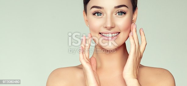 Brown haired woman with clean fresh skin is touching the face. Young, attractive model is smiling wide and shows  teeth braces. Dental health , stomatology, teeth care, medical help and beauty technology.