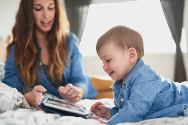 Young attractive mother with female toddler child teaching to read on tablet in cosy bed stock photo