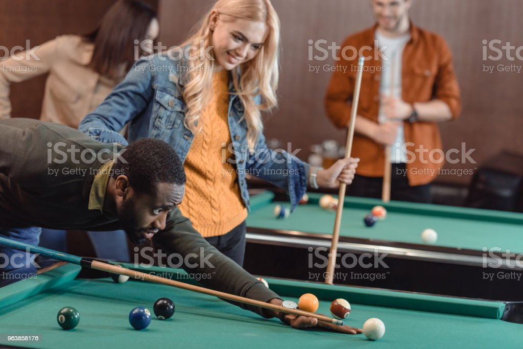 young attractive multiculture friends playing in pool at bar - Royalty-free Adult Stock Photo