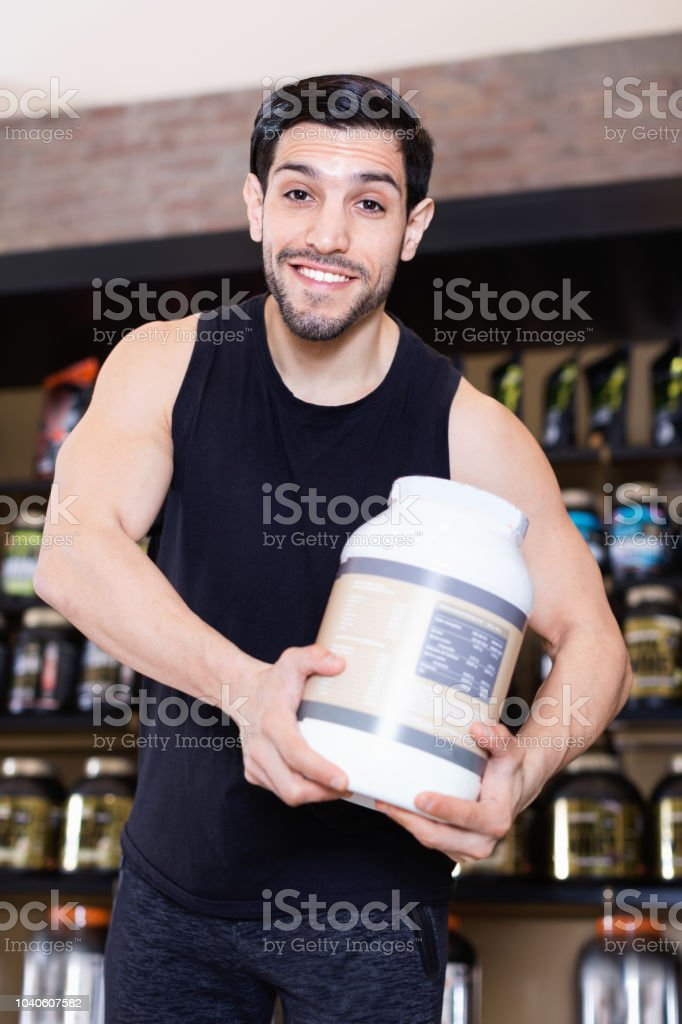 Young attractive muscular man showing his power and holding pot of  sport nutrition stock photo