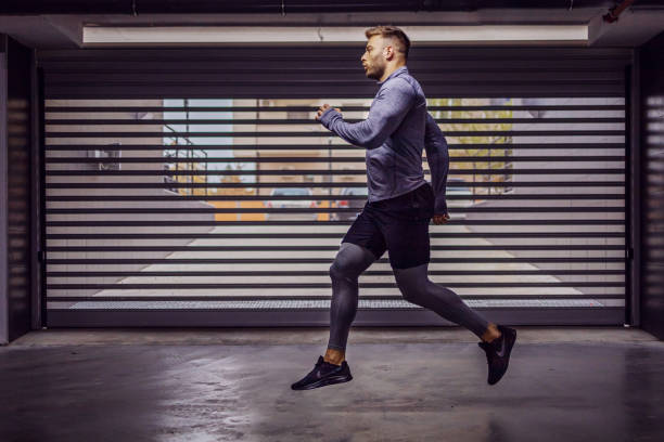 young attractive muscular sportsman running in underground garage. - man city exercise abs foto e immagini stock