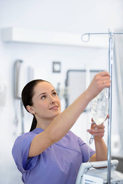 Young attractive nursing starting an IV stock photo
