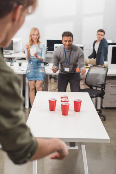 junge attraktive menschen spielen bier pong im modernen büro nach der arbeit - lustige trinkspiele stock-fotos und bilder